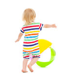 Baby in swimsuit playing with ball. Rear view Royalty Free Stock Image
