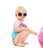Baby in swimsuit and sunglasses playing with ball Royalty Free Stock Photography