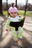 Baby in a Swing. An infant in a playground swing with a protective helmet Stock Photography