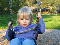 Baby on swing. A young blond baby girl in a playground swing Stock Photo
