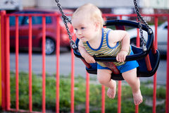 Baby on a swing. Babyboy sitting in a swing and having fun Royalty Free Stock Photo