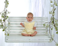 Baby on Swing. Smiling baby boy sitting on swing Stock Photo