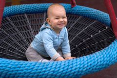 Baby-swing. A baby is playing on a playground, he is sitting in a baby-swing Stock Photos