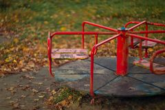 Baby swing in the fall in the park in wet weather royalty free stock photography