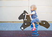 Baby swing on horse on playground Stock Photo