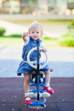 Baby swing on horse and pointing in camera Royalty Free Stock Photography