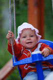 Baby swinging. A beautiful little caucasian baby girl with cute smiling facial expression swinging on a swing outdoors royalty free stock images