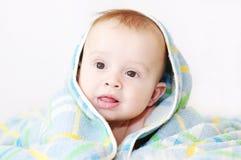 Baby täckte vid den blåa handduken Arkivfoto