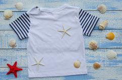 Baby  t-shirt and seastars on Shabby Chic blue and white wooden background Stock Photo