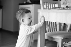 Baby by table Stock Photography