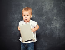 Baby with tablet computer in the hands of empty chalkboard royalty free stock photo