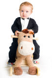 Baby in tailcoat on rocking horse Royalty Free Stock Image