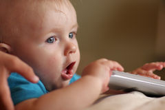 Baby takes remote control Stock Photo