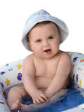 Baby Taking A Bath. Cute baby in a hat taking a bath Royalty Free Stock Images