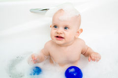 Baby taking bath and playing with toys Stock Photo