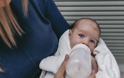 Baby taking feeding bottle Stock Images