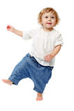Baby taking first steps. The child dances on a white background, lifted his leg, walks, indulge in, runs royalty free stock photography