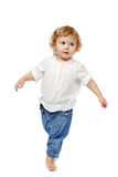 Baby taking first steps. The child dances on a white background, lifted his leg, walks, indulge in, runs stock images