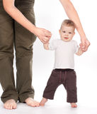 Baby taking first steps with father help on white Stock Photo