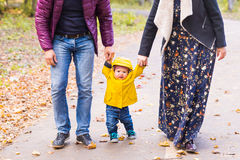 Baby taking first steps with father and mother help in autumn garden in the city Stock Images