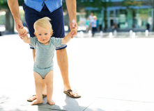 Baby taking first steps with fathers help Stock Photography