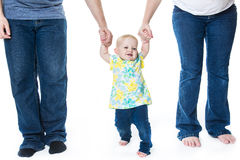 Baby taking first steps with mother father help on white background Royalty Free Stock Images