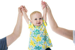 Baby taking first steps with mother father help on white background Stock Image