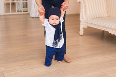 Baby taking first steps with mother help.  royalty free stock image