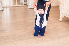 Baby taking first steps with mother help.  stock images