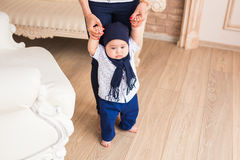 Baby taking first steps with mother help.  royalty free stock photo