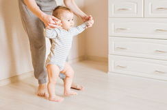 Baby taking first steps with mother help Stock Photography