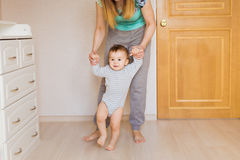 Baby taking first steps with mother help. In the bedroom royalty free stock image