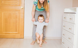 Baby taking first steps with mother help. Indoors royalty free stock photography