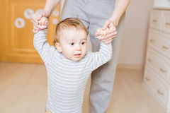 Baby taking first steps with mother help. Indoors royalty free stock image
