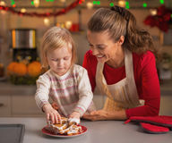 Baby taking homemade christmas cookies from plate Royalty Free Stock Image