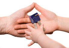 Baby taking keys from parents' hands. Isolated at the white background Stock Photos