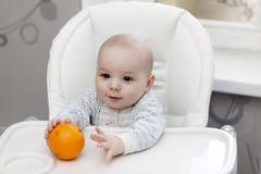 Baby taking orange Stock Photography