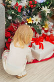 Baby taking present from under Christmas  tree Stock Images