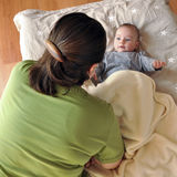Baby talk. Women talking to a baby lying on a bed; shot from above Stock Photos