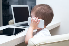 Baby talking on a cell phone at home Stock Images