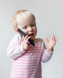 Baby talking over phone Royalty Free Stock Images