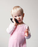 Baby talking over phone. Cute adorable white Caucasian blond baby with blue eyes talking expressively emotionally over mobile cell phone with funny expression on Royalty Free Stock Image