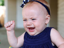 Baby tantrum. Adorable baby girl having a tantrum, cries with arm raised in anger royalty free stock images