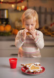 Baby tasting homemade christmas cookies in kitchen Stock Photos