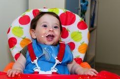 Baby täckte med mat efter matställe Arkivbilder