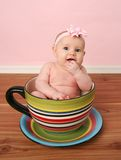 Baby in a tea cup. Portrait of cute baby girl sitting inside a giant tea cup or mug