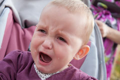 Baby with tears streaming down stock photo