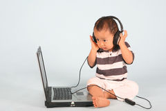 Baby and Technology. Baby with headphone listens to a song Royalty Free Stock Photo