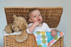 Baby and Teddy. Image of cute baby and teddy bear peeking out of a wicker trunk Royalty Free Stock Image