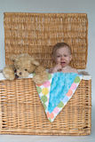 Baby and Teddy. Image of a cute, fussy baby and a teddy bear peeking out of a wicker trunk Stock Image